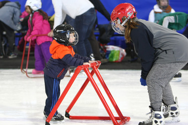 Photo of kids wearing helmets and skates learning ice-skating in a rink