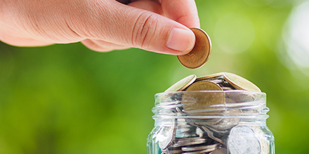 A person's hand placing coins into a jar symbolizing saving small amounts of money.