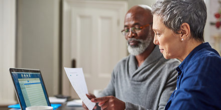 Elderly man and woman sitting at a table reviewing financial statements symbolizing retirement planning.