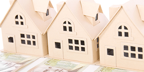 Three cardboard houses, each sitting on a $100 bill, symbolizing real estate investments.