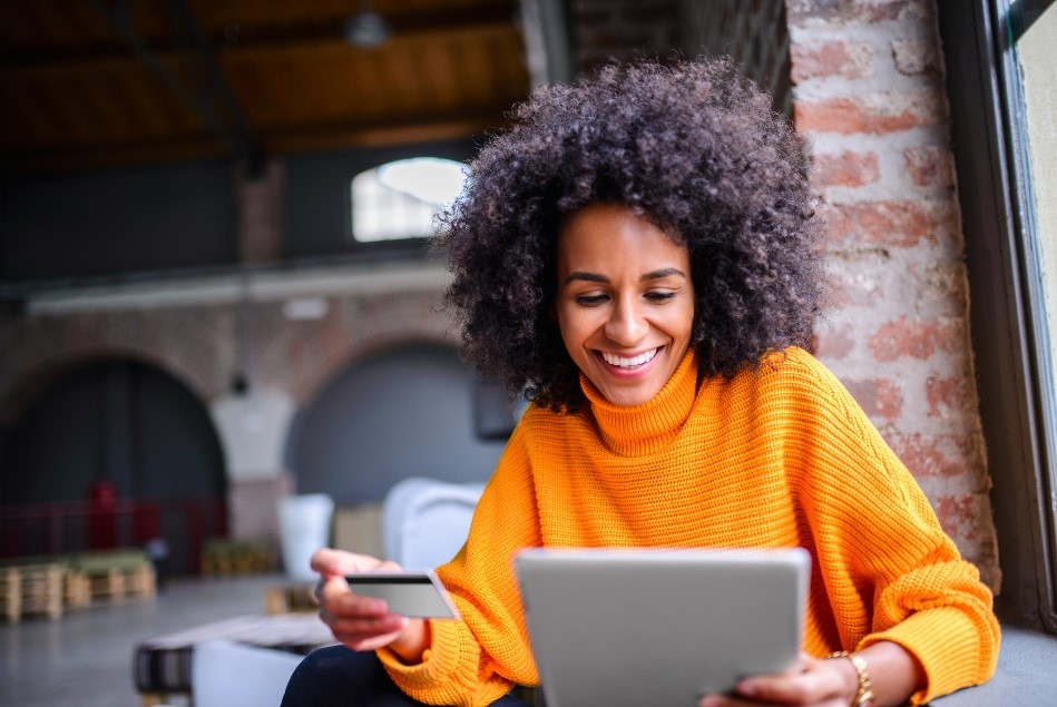 Woman in orange turtleneck sweater is sitting in a brick warehouse type space, holding a tablet in her left hand and a credit card in her right. She is smiling and looks like she might be reading the information on the front of her credit card to do some online shopping.