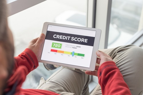 "An over-the-shoulder view of a man holding a tablet in his lap. He wears beige pants, a red long sleeve shirt but is otherwise unidentifiable. The tablet shows the bold headline ""Credit score"" and illustrates a credit score of 720 along a rainbow-hued scale of scores (red, orange, yellow, light green, green). 720 is shown on the light green section of the scale. ""Credit rating: good"" is also displayed."