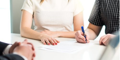Image shows two torsos: a feminine and a masculine, sitting together at a white table. There are papers on the table and the masculine arm holds a pen positioned as if to sign a document. The feminine arms are resting on the table and red nail polish is featured. In the lower left corner you can see two additional masculine hands clasped together. This is all you can see of the people.
