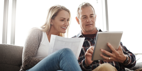 Couple sitting together looking at an iPad reviewing their financials