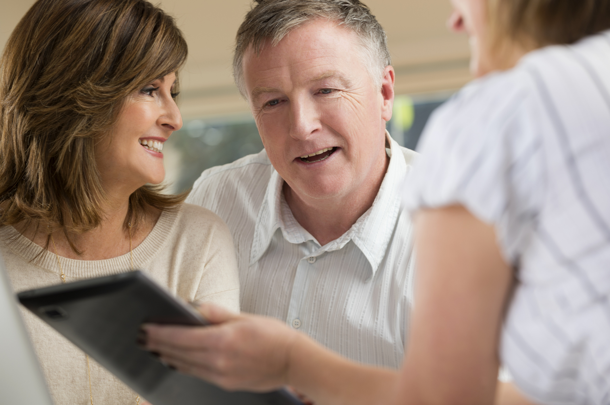 Advisor reviewing information on an ipad with happy couple