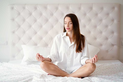 Woman sitting on bed with her legs crossed meditating