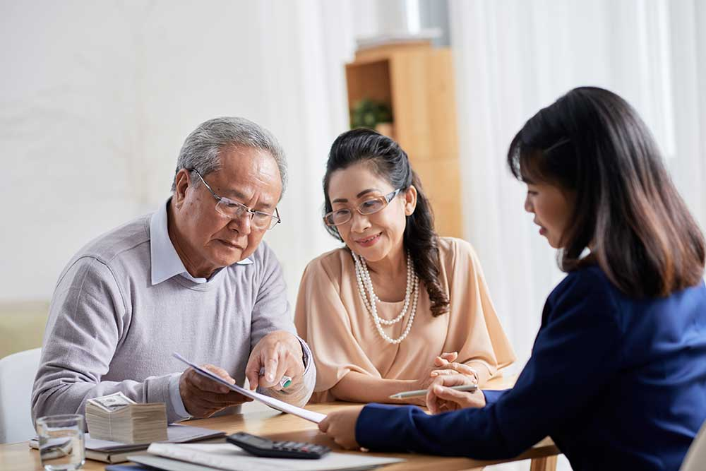 Image of an older Asian-Canadian couple sitting with their financial advisor (a woman in her 40s). The couple is facing the camera but looking at paperwork they're holding, the financial advisor is facing the couple and we see her from the back and side.