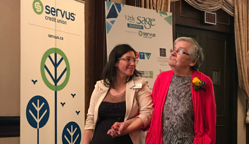 A Servus representative and a Sage Senior's Award recipient