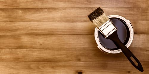 Photo of a paintbrush and a can of paint on a wooden floor