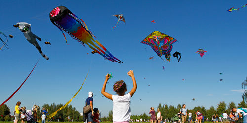 Photo of people flying giant kites in a kite festival