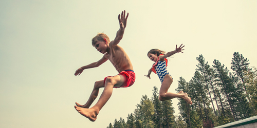 Two children jumping into a lake