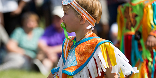 Image from a past Servus Heritage Festival: a young child dressed in costume standing in front of a crowd lounging on the grass.